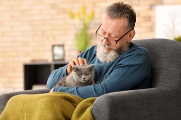 Senior man holding cute cat at home