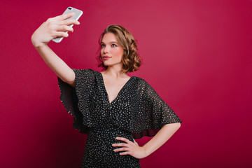 Indoor photo of attractive young lady in vintage dress making selfie on claret background. Wonderful caucasian girl holding smartphone and taking picture of herself in her room.