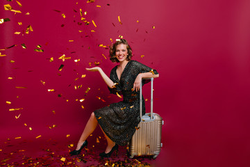 Pretty girl in elegant shoes sitting on suitcase ready to vacation. Indoor portrait of excited female model in long dress posing under confetti with luggage.