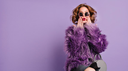 Spectacular young woman with trendy makeup posing with surprised face expression on bright purple...