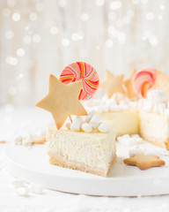 "Classic cheesecake ""New York"" with a xmas decor: ginger cookies, marshmallow and candy on a light wooden Christmas background with gifts and lights. Winter xmas holidays concept."