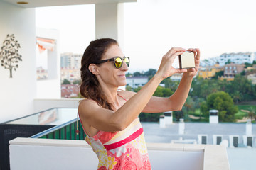 elegant adult woman, with red dress and sunglasses, taking a photo or video recording with a smartphone in the terrace. Behind green nature and houses