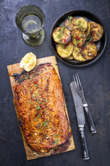 Barbecue salmon fillet marinated on cedar plank wood with fries as overhead view