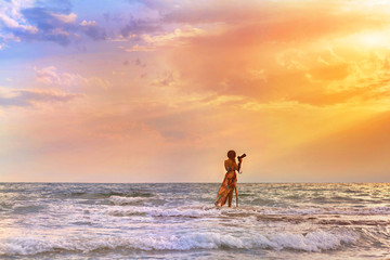 Female photographer with professional camera standing in the sea and takes picture of sunset. Female in the dress in the waves of ocean on sunset background
