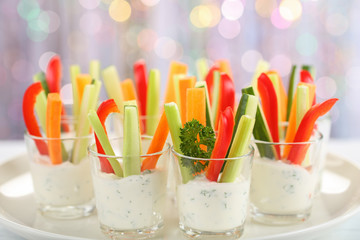 Verrines appetizer with carrot, cucumber, celery and red bell pepper sticks in glasses on platter at bokeh background, view from above, close-up