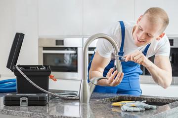Happy plumber repairing kitchen's faucet