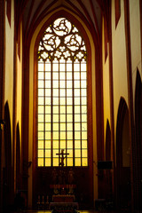 Stunning gorgeous sunset light through an old medieval Gothic church window in Europe.