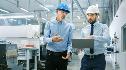 Head of the Department Holds Laptop and Discuss Product Details with Chief Engineer while They Walk Through Modern Factory. Wall mural