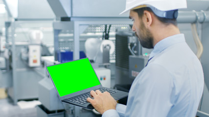 Close-up of the Engineer Holding Laptop with Green Screen Chroma Key Template Great for Mockup. In the Background Modern Factory Equipment.