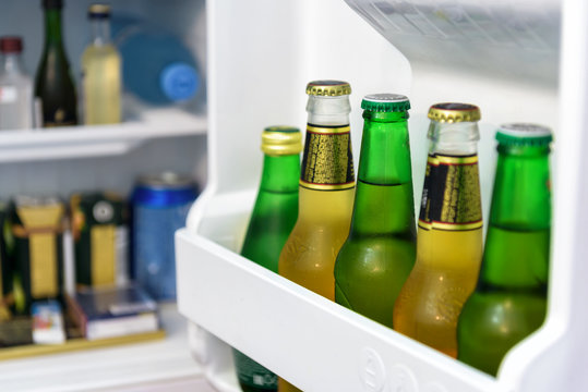 Mini fridge full of bottles in hotel room, the open door of refrigerator