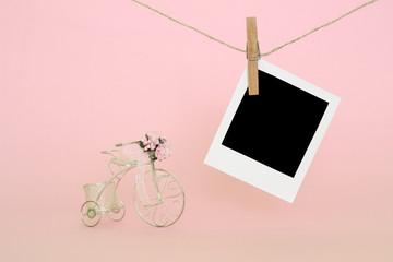 Pembe fon üzerinde minyatür bisiklet ve fotoğraf kartı / Miniature bicycle and photo card on pink background