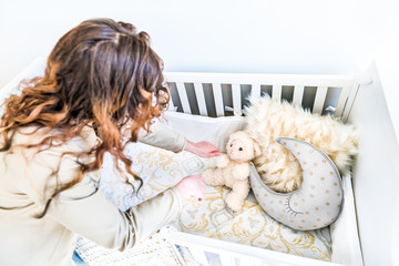 Closeup of bright yellow baby crib in nursery room with young woman in model staging home, apartment or house setting-up cot