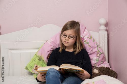 Mädchen liest auf ihrem Bett  Stockfotos und lizenzfreie