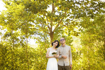 Couples standing walk arm in arm on the green forest background.