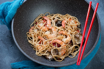 Wok pan with stir-fried udon noodles and tiger shrimps, selective focus, studio shot