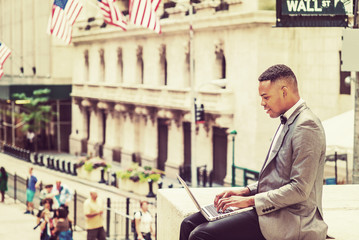 Happy African American Businessman traveling, working in New York. Wearing gray blazer, bow tie, college student siting on Wall Street, reading, working on laptop computer. Retro filtered effect..