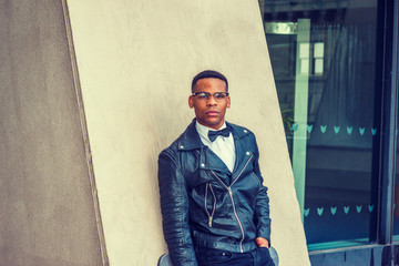 Man Urban Autumn/Spring Casual Fashion. Wearing black leather jacket, white undershirt, black bow tie, sunglasses, African American guy standing against wall on street in New York. Filtered effect..