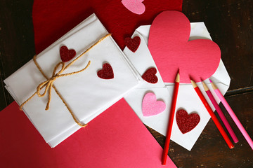 Art Supplies and Envelopes Layed out On a Table Making a Paper Heart Valentine