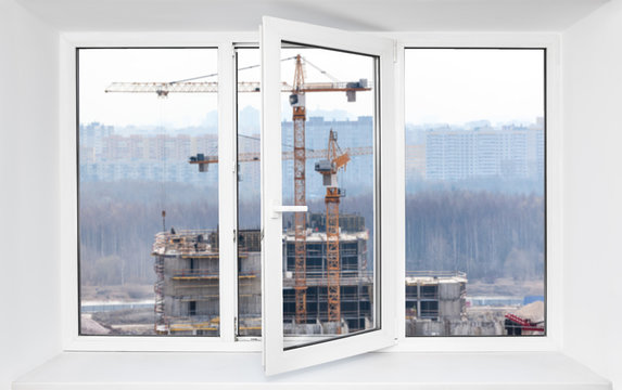 Loud construction site noise immission in opened one frame of pvc window, view through
