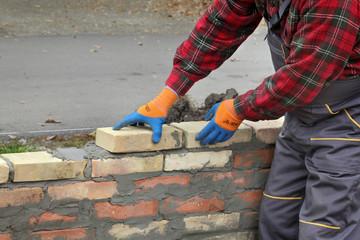 Mason worker making wall with mortar and bricks, closeup of hands placing brick