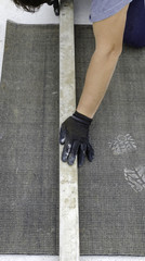 Worker cutting a bituminous membrane to be used to waterproof an external surface (terrace, balcony, etc.)