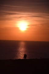 Sun sets over couple taking a romantic stroll