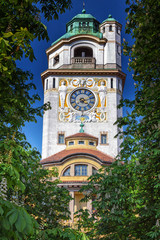 Turm mit Uhr des Müllerschen Volksbades in München umrahmt von Kastanien