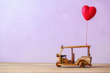 valentine 's day with a red heart and a tuk tuk car Thailand toy on wood table , coy space for texture