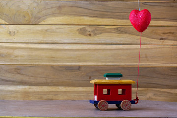 valentine 's day with a red heart and a car toy on wood table , coy space for texture