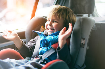 Portrait of pretty toddler boy sitting in car seat. Child transportation safety Wall mural