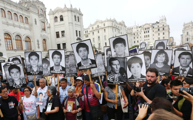 People holding pictures of victims of the guerrilla conflict in the 80s and 90s march against President Pedro Pablo Kuczynski's pardon for former president Alberto Fujimori in Lima