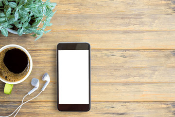 Smartphone white screen, white ear phone and cup of coffee on wooden table background