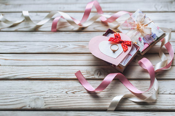 A wedding ring on a gift box with ribbons and hearts on a wooden background. A gift for Valentine's Day. Festive decor. View from above. Marriage proposal. Copy space.
