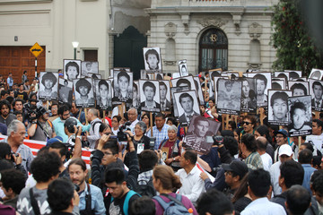 People holding pictures of victims of the guerrilla conflict in the 80s and 90s march against President Pedro Pablo Kuczynski's pardon for former president Alberto Fujimori in Lima, Peru
