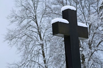 Winter scene of Christian stony cross at a cemetery and trees in the background covered with snow