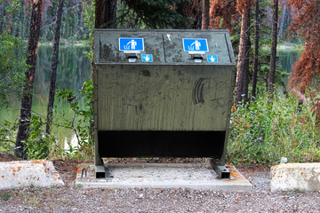 a bear proof garbage container along side a parking lot