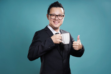 Businessman in suit smile and enjoy cup of coffee with thumb up gesture.