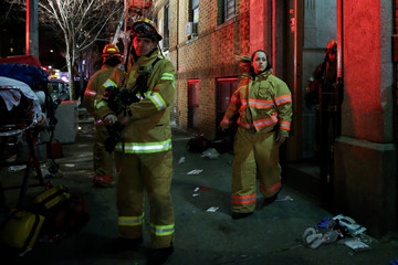 Fire Department of New York (FDNY) personnel work on the scene of an apartment fire in New York