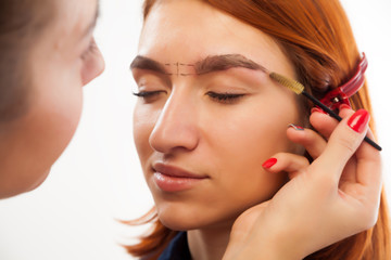 The procedure for eyebrow correction in the beauty salon. The make-up artist penciled an ideal eyebrow shape on a young red-haired woman and combs them with a special brush on a white background