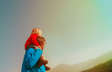 Father and little daughter travel in mountains looking at view