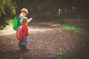 little boy and girl travel hiking in nature looking at map
