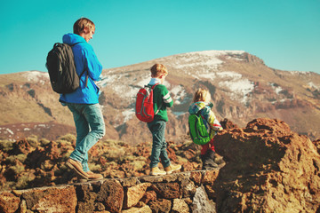 father and three kids travel hiking in mountains