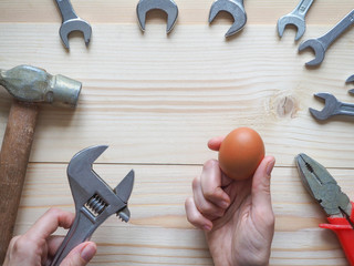 Hand, tool and egg on wooden background. The concept of complex problems, the challenge can be solved.