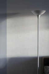 A white floor lamp against a wall background.