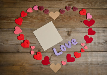Word Love composition on the wooden board surface and many hearts handmade around.