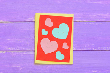 Valentines day or Mothers day paper card with pink and blue hearts. Greeting card isolated on a wooden background. Cool paper crafts for kids. Top view