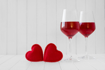 Valentines Day still life with hearts and glasses of wine over white background