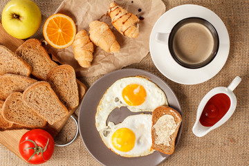 Plate with fried eggs and toast with butter, cup of coffee, croissants, orange, apple, bread on wooden cutting board, fresh tomato and ketchup in a sauce boat