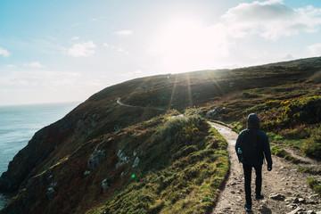 Tourist walking on sunny hill