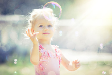 A little girl catches soap bubbles in summer park